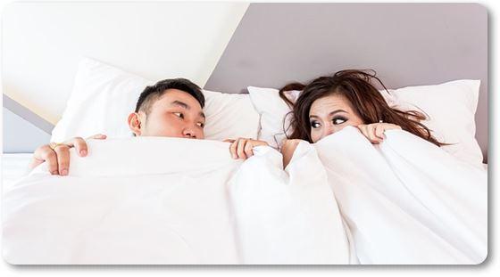 Pareja escondida en la cama preocupados por las ladillas